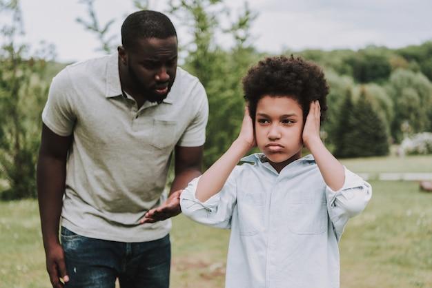 Chłopiec zamyka uszy i odwrócił się od ojca.