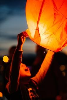 Chłopiec zapala tradycyjne papierowe lampiony podczas zachodu słońca