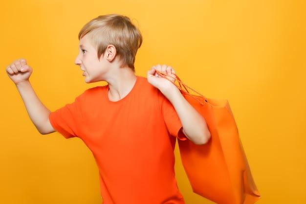 Chłopiec zarzucił na plecy pomarańczę i papierową torbę na zakupy i pokazuje pięść na bok