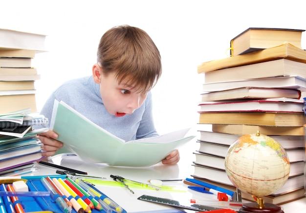 Chłopiec zaskoczył za stołem z książkami