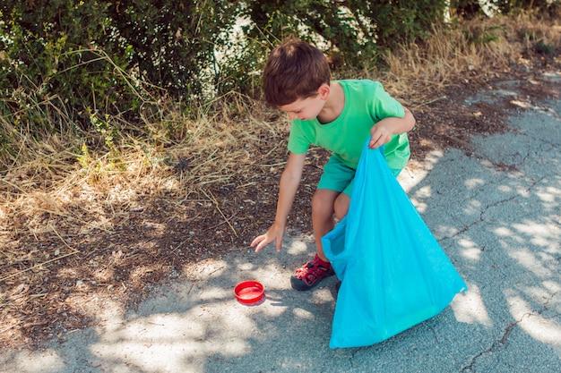 Chłopiec zbiera śmieci w parku podczas gdy trzymający błękitną plastikową torbę