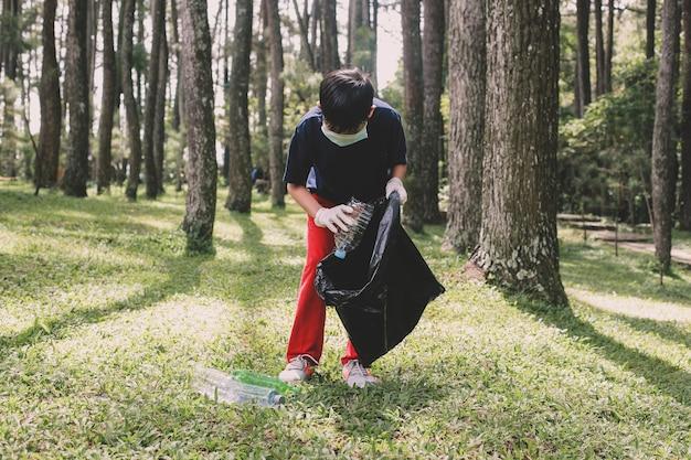 Chłopiec zbiera śmieci z plastikowych butelek w lesie i wrzuca je do worka na śmieci