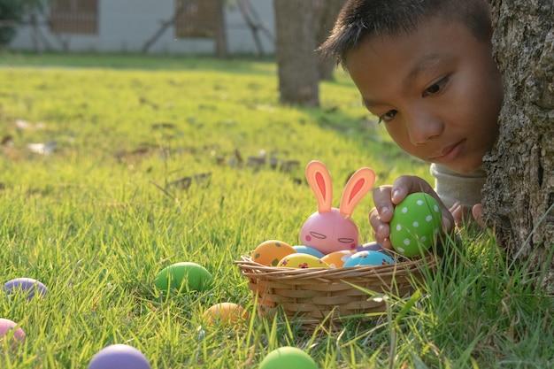 Chłopiec zbierający kolorowe jajko w parku.