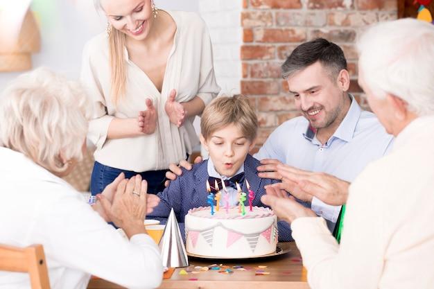 Chłopiec zdmuchujący świeczki