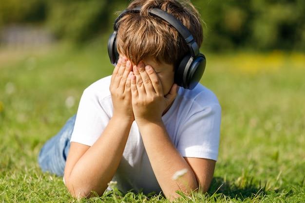 Chłopiec ze słuchawkami, słuchając muzyki, leżąc na trawie w parku