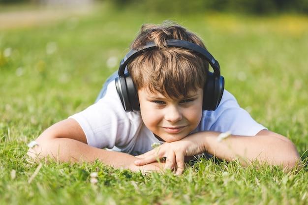 Chłopiec ze słuchawkami, słuchając muzyki na trawie