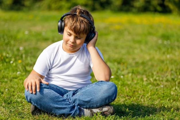 Chłopiec ze słuchawkami, słuchając muzyki, siedząc na trawie w parku