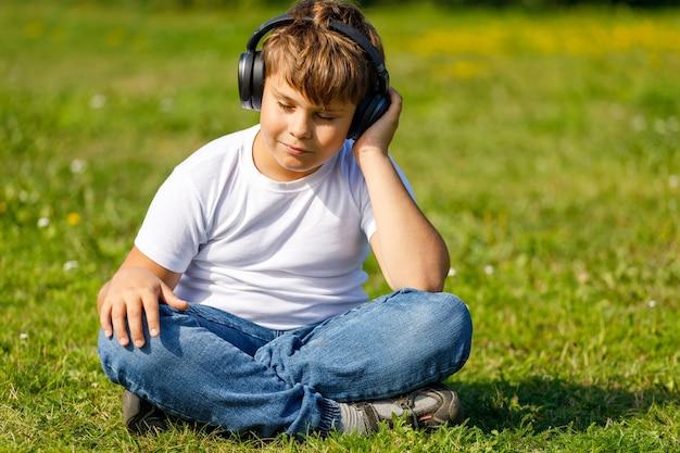 Chłopiec ze słuchawkami, słuchając muzyki, siedząc na trawie