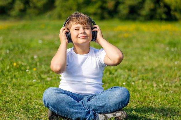 Chłopiec ze słuchawkami, słuchając muzyki siedząc na trawie