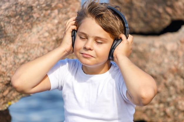 Chłopiec ze słuchawkami, słuchanie muzyki na świeżym powietrzu