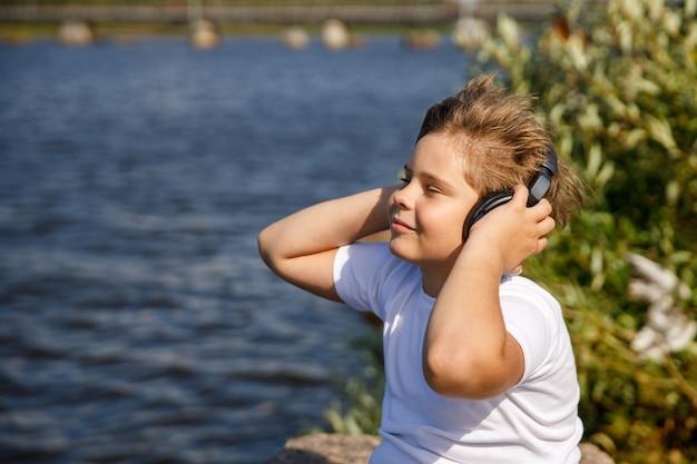 Chłopiec ze słuchawkami, słuchanie muzyki nad jeziorem