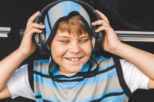 Chłopiec ze słuchawkami, słuchanie muzyki obok samochodu