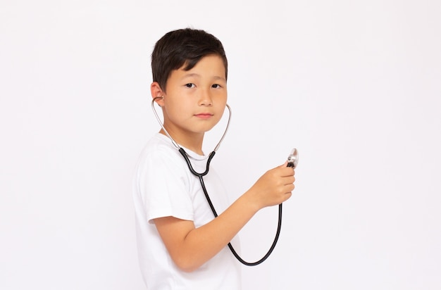 Chłopiec ze stetoskopem w białej powierzchni