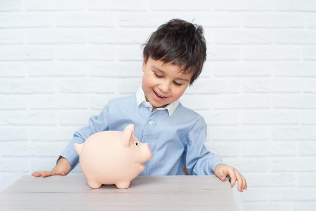 Chłopiec ze świnką-skarbonką. koncepcja dzieciństwa, pieniędzy, inwestycji i szczęśliwych ludzi
