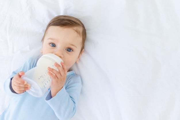 Chłopiec zjada mleko z butelki na łóżku przed pójściem spać w niebieskim body, koncepcja jedzenia dla niemowląt