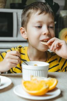 Chłopiec zjada rano śniadanie ze zbóż z mlekiem. rano śniadanie w kuchni przed szkołą. chłopiec je przy stole pod oknem.