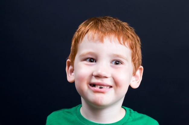 Chłopiec zjadł pysznego słodkiego arbuza i kości w ustach, zbliżenie portret chłopca z rudymi włosami