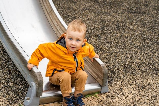 Chłopiec zjeżdżający ze zjeżdżalni na placu zabaw