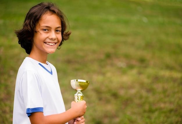 Chłopiec zwycięża po meczu piłki nożnej z miejsca na kopię