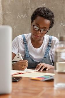 Chłopięca kobieta z krótką fryzurą i czarną skórą, robi notatki w pomieszczeniach