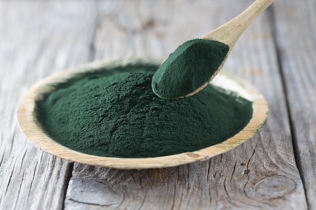 Chlorella jednokomórkowe zielone algi. detox pożywienie na drewnianym talerzu