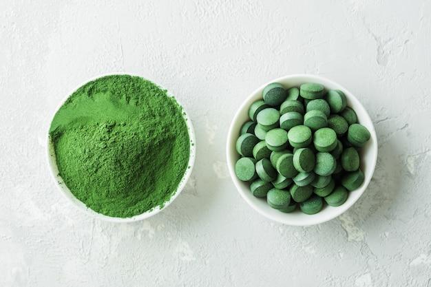 Chlorella lub spirulina w postaci tabletek i proszku na szarym betonowym tle.
