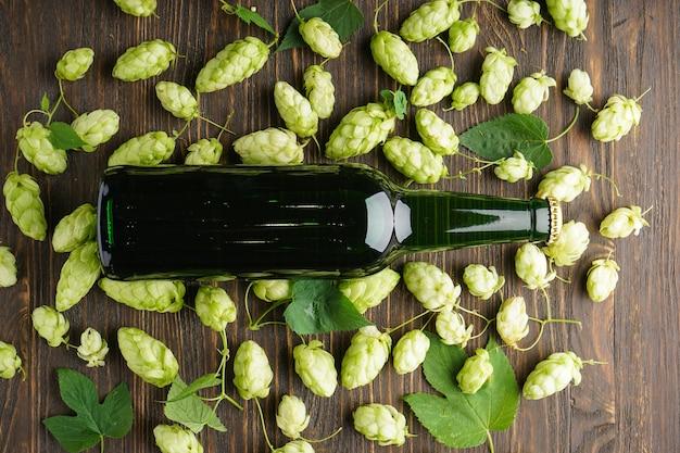 Chmiel i piwo jasne w butelce na drewnianej przestrzeni, leżały na płasko.