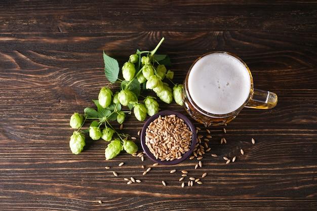 Chmiel i szklanka jasnego piwa na drewnianej przestrzeni. widok z góry.