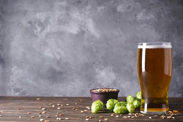 Chmiel i szklanka jasnego piwa na szarej przestrzeni, miejsce na tekst.