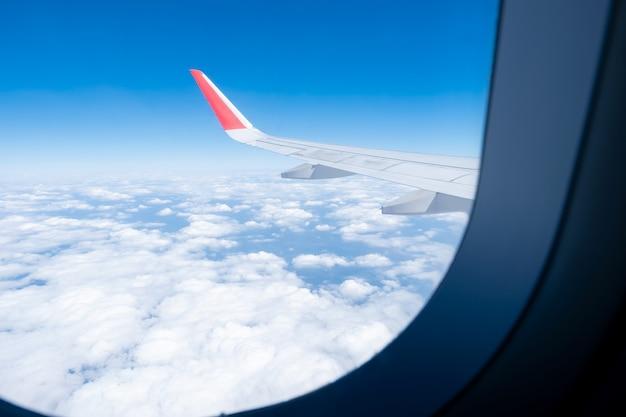 Chmura, błękitne niebo i skrzydło samolotu widziane przez okno widoku samolotu.
