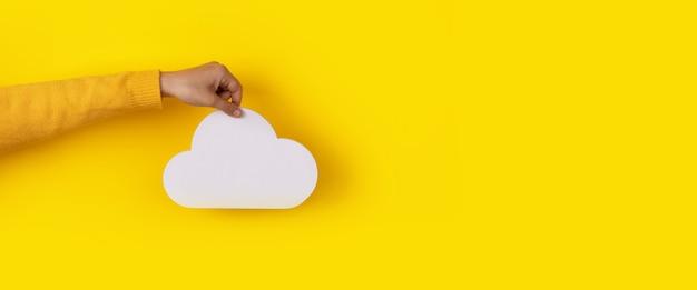 Chmura do przechowywania w ręku na żółtym tle, koncepcja przechowywania, układ panoramiczny