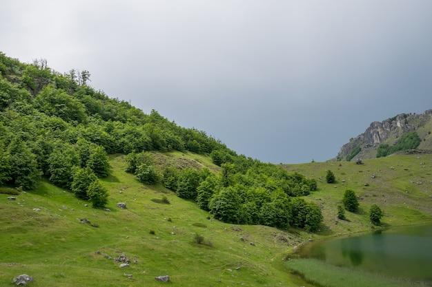 Chmury deszczowe zbliżają się do górskiego jeziora.