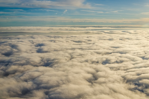Chmury i niebo widziane przez okno samolotu.