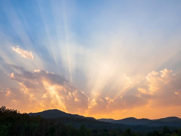 Chmury i promienie słońca nad górami wieczorem.