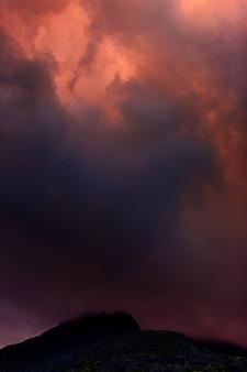 Chmury na niebie nad górami oświetlone przez słońce o zachodzie słońca