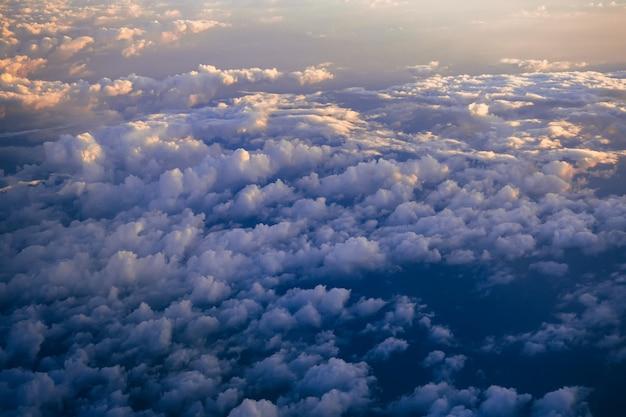 Chmury na niebieskim niebie ze światłem słonecznym z samolotu