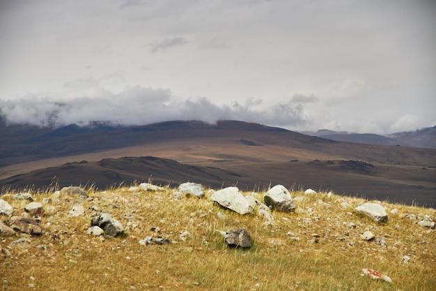 Chmury nad stepowymi otwartymi przestrzeniami, chmury burzowe nad wzgórzami. płaskowyż ukok na ałtaju. bajeczne zimne krajobrazy. ktoś w pobliżu