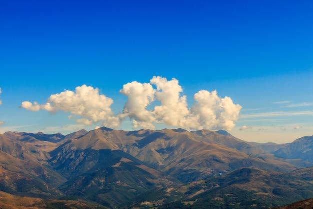 Chmury o ciekawych kształtach na szczycie góry