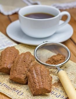 Choco madeleines w proszku kakaowe z filiżanką kawy