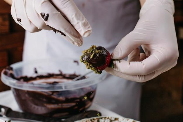 Choco truskawkowy kucharz zanurzanie czerwonej truskawki wewnątrz czekolady