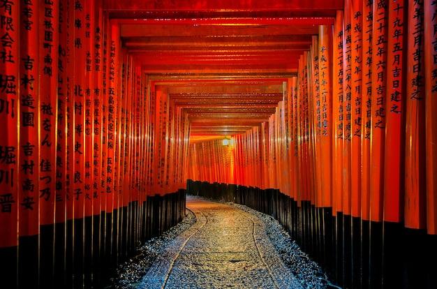 Chodnik z czerwonymi bramami torii w świątyni fushimi inari taisha w kioto w japonii.