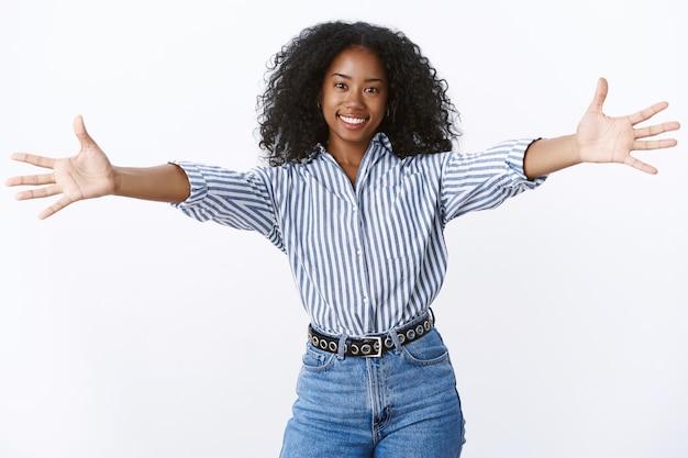 Chodź, daj się przytulić. portret przyjaźnie wyglądająca atrakcyjna afroamerykańska przyjaciółka daje ciepłe powitanie chce objąć przytulić, rozciągnąć ramiona na boki uśmiechając się szeroko witając gości, biała ściana
