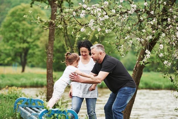 Chodź do mnie. wesoła para spędza miły weekend na świeżym powietrzu z wnuczką. dobra wiosenna pogoda