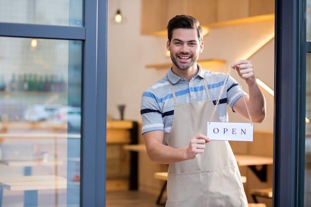 Chodź tu. wesoły przystojny brodaty mężczyzna stojący przy drzwiach i trzymając etykietę, zapraszając do kawiarni