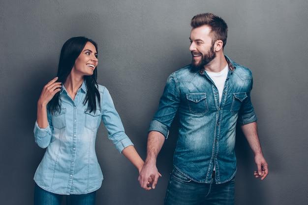 Chodź za mną! strzał studio pięknej młodej pary w dżinsach chodzić razem i trzymając się za ręce