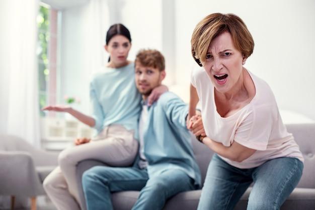 Chodź ze mną. nieszczęśliwa zła matka trzymająca syna za rękę, pragnąc jego uwagi