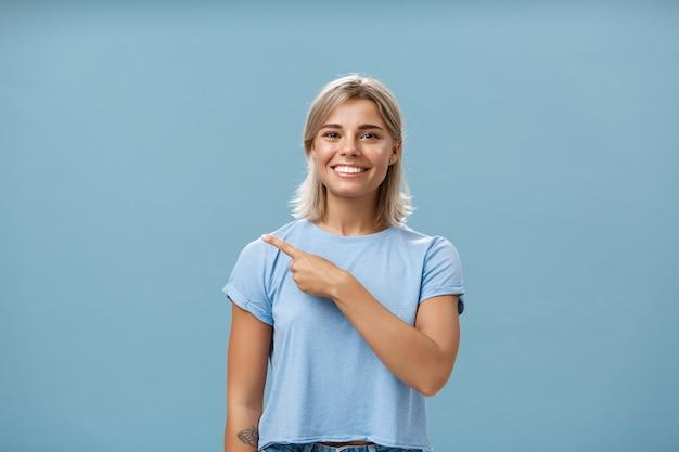 Chodź ze mną. portret stylowej zadowolonej, przystojnej studentki o blond włosach w modnej koszulce, wskazującej na lewy górny róg i uśmiechającej się z zachwytem i szczęściem pozowanie