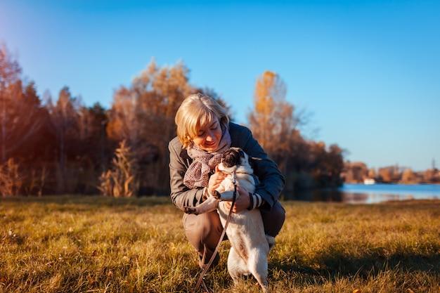 Chodzący mopsa pies w jesień parku rzeką. szczęśliwa kobieta przytulanie zwierzaka i zabawy z najlepszym przyjacielem.
