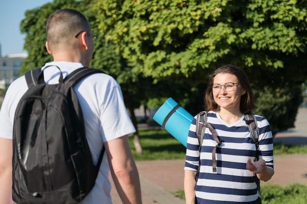 Chodzący na zewnątrz mężczyzna i kobieta, rozmawiający ludzie w średnim wieku para