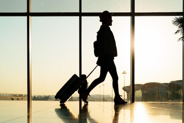 Chodzący podróżnik z walizką, pasażer na wycieczkę w terminalu lotniska do podróży lotniczych